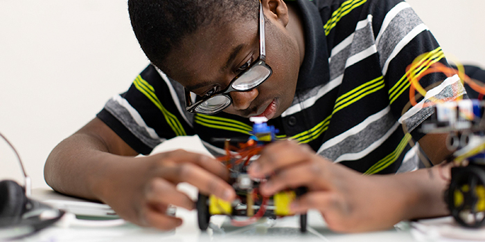 A student focuses on a robotics project at a US Quest Forward Academy.