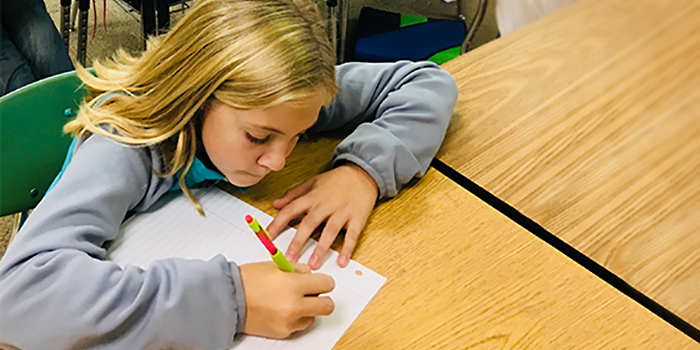 A student writes a pen-pal letter to a Sister School student at her desk with a colorful pencil and lined paper.
