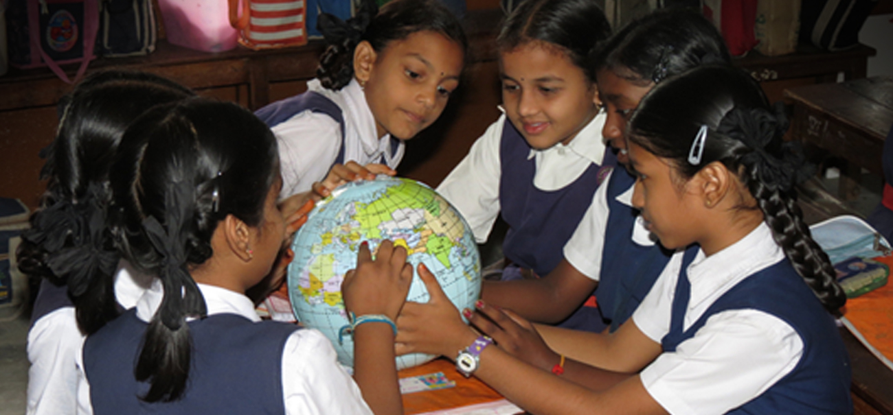 A group of primary school girls surround a globe and smile while pointing to locations on it.