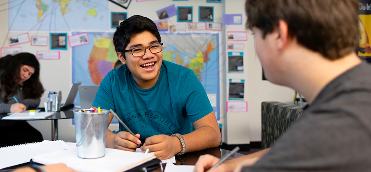 A high school student smiles brightly while having a discussion with a classmate at Quest Forward Academy in Omaha, Nebraska USA.
