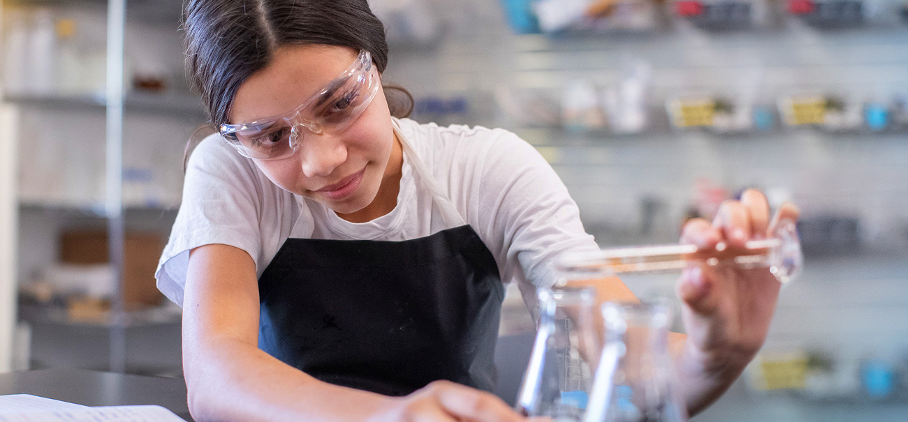 A female student at Quest Forward Academy Santa Rosa smiles slightly while she focuses and carefully pours a liquid into a beaker.