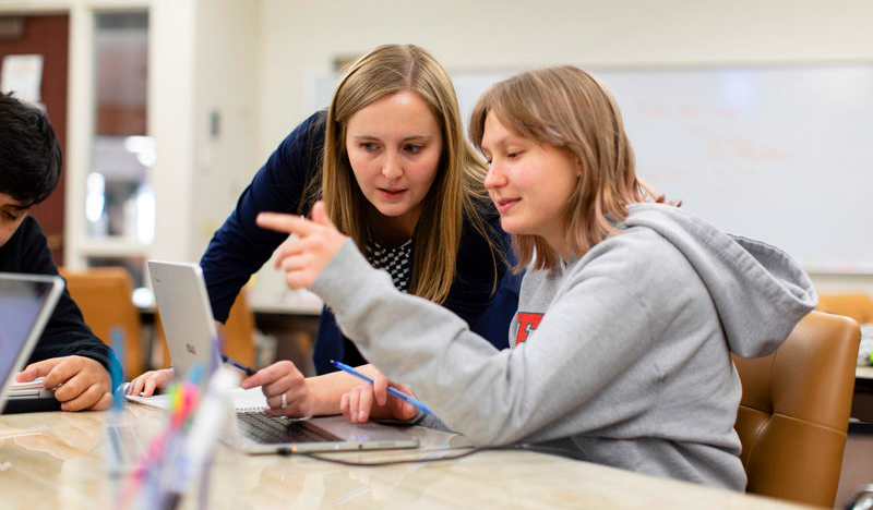 A mentor and student collaborate closely together, the student smiling while gesturing assertively toward her laptop.