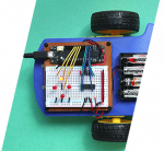 A colorful photo of a circuit board with wheels and batteries represents the coding course for Summer Explorations at Quest Forward Academy Omaha.