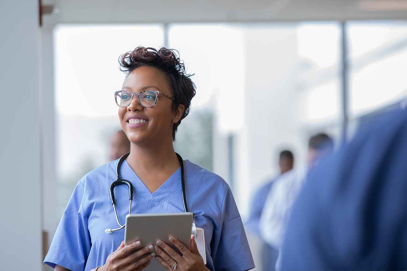 A young, female nurse or doctor smiles while staring out window in hospital hallway and holding a digital tablet.