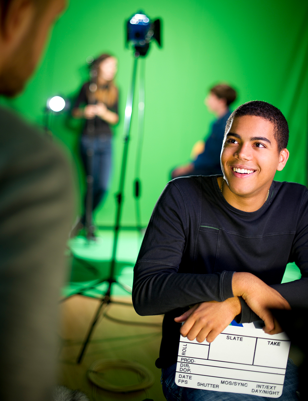 A student smiles while looking up at an internship colleague on a film set, with a green screen and lighting behind them.