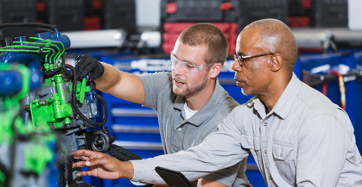 A technician and his apprentice work on a diesel engine together.
