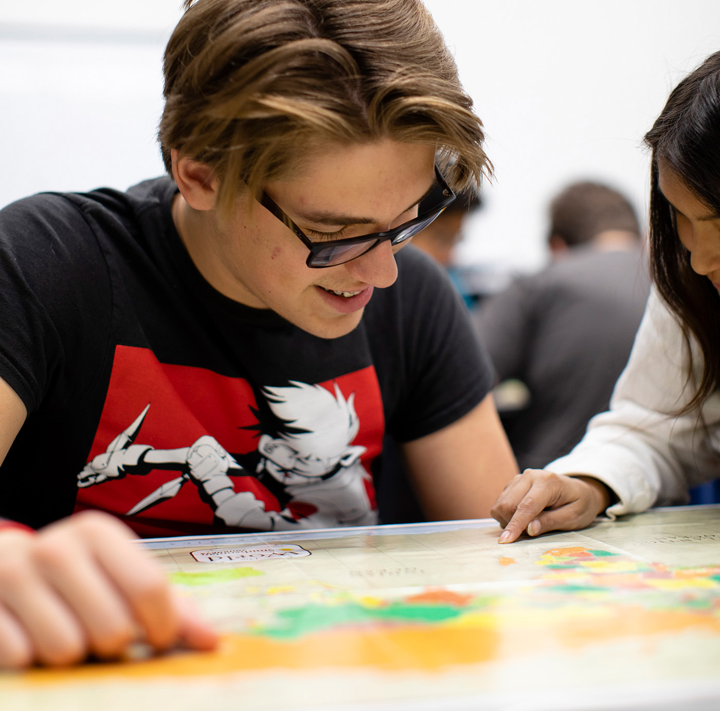 A student smiles while examining a world map.