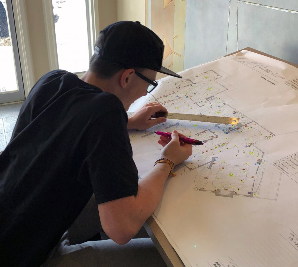 Quest Forward Academy student Graysen smiles at a desk with blueprints during his internship through the Pathways Program.