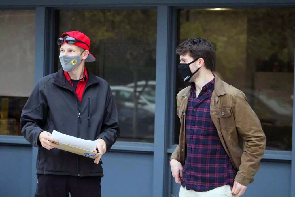 Quest Forward Academy mentors Nils Palsson and Max Shafer-Landau wear masks and hold clipboards while they stand outside the school to greet students for in-person learning.