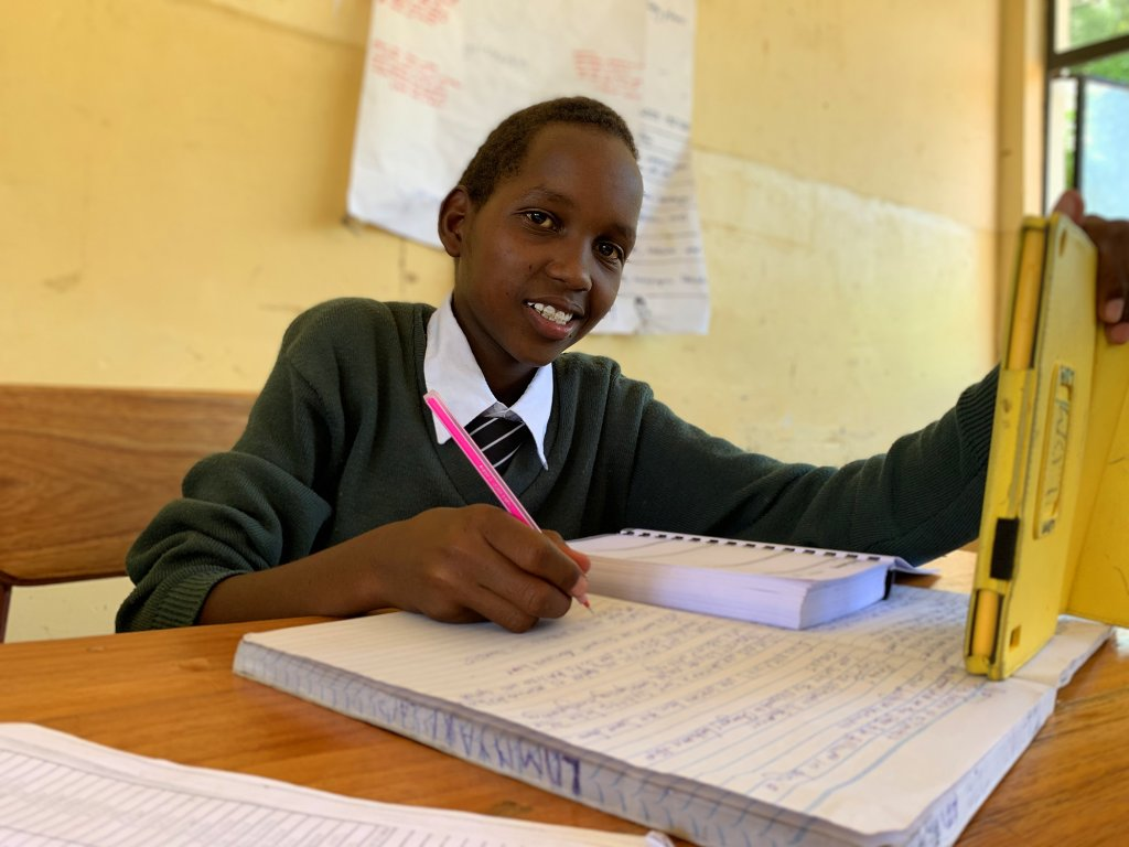 A smiling student at Mtakuja Secondary School holds a tablet with the Quest! app and takes notes in a notebook.